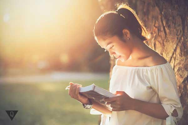 Девушка читает книгу под деревом