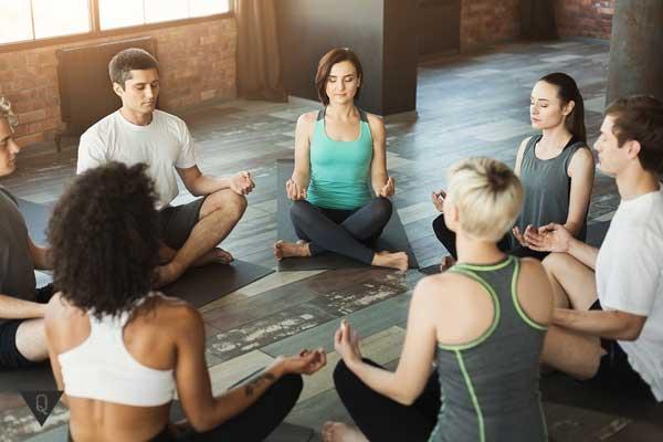 Группа людей сидит в кругу, медитируя