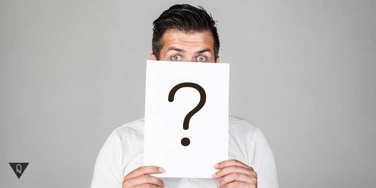 Мужчина держит лист со знаком вопроса, как символ того, какие качества скрываются за ним