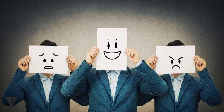 Мужчины держат листы бумаги с нарисованными смайлами, что символизируют различное настроение
