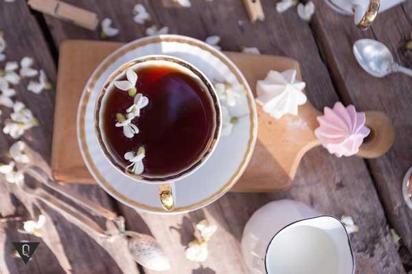Чашка чая на разделочной доске, украшенная цветами