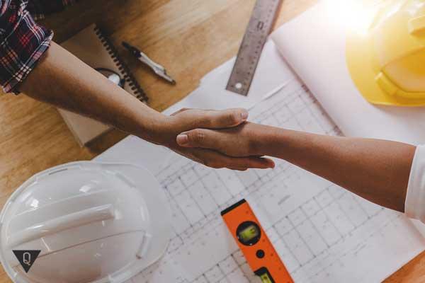 Два работника пожимают друг другу руку