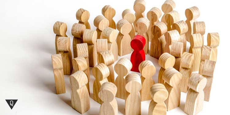 Деревянные фигурки взяли в круг одну красную фигуру, которая является лидером