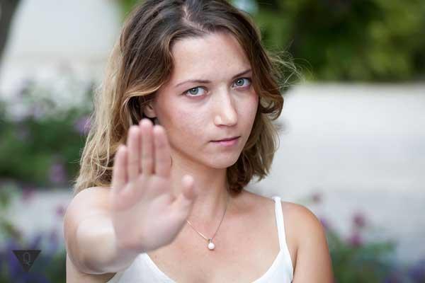 Девушка выставила вперёд руку в знак отказа и несогласия.