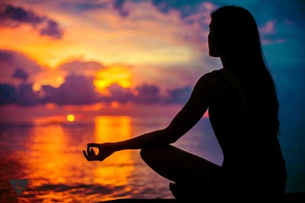 Женщина медитирует на берегу моря на закате