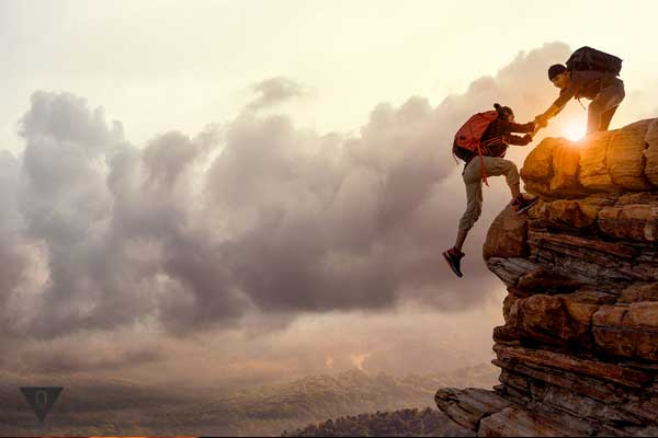 Мужчина помогает подняться женщине на гору