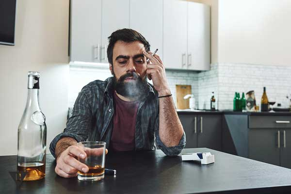 Зависимый от алкоголя и сигарет мужчина