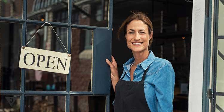 Женщина улыбается открывая магазин