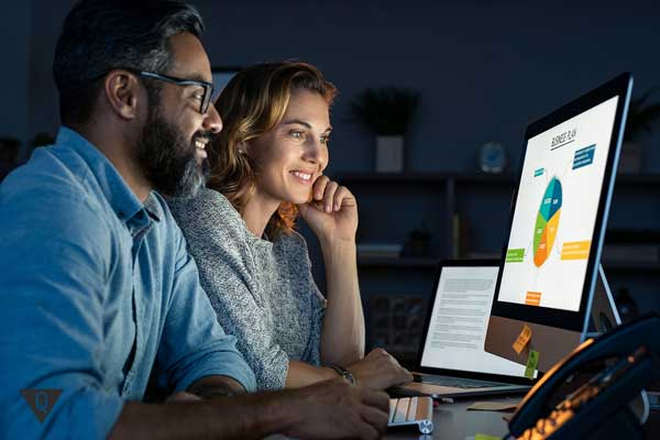 Пара улыбается, смотря в компьютер