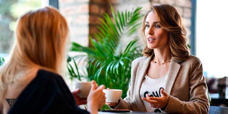 Две девушки общаются за столом