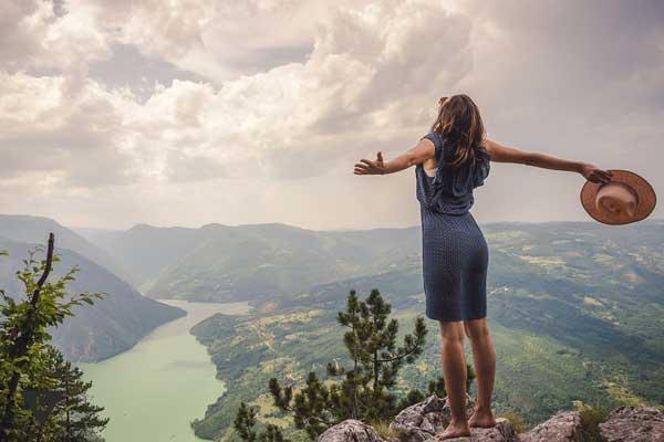 Девушка стоит на вершине горы