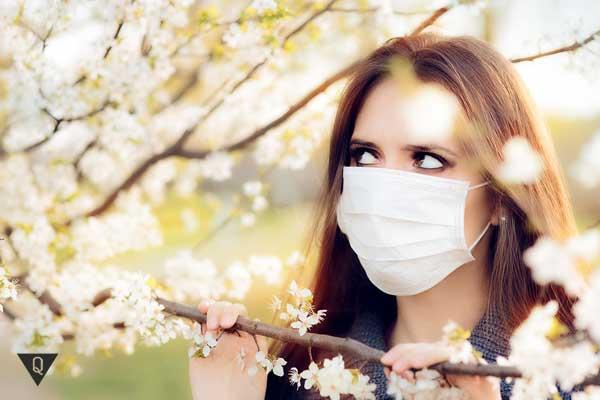 Девушка в маске подозрительно смотрит на цветы