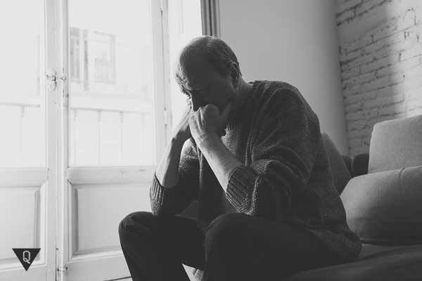 Расстроенный мужчина сидит на диване