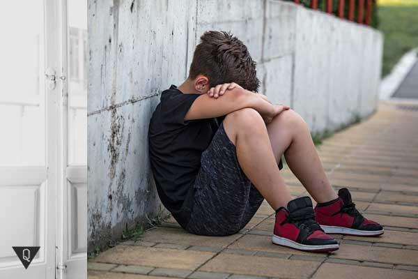 Мальчик плачет сидя на тратуаре