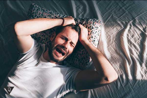 Мужчина плачет лежа на кровати