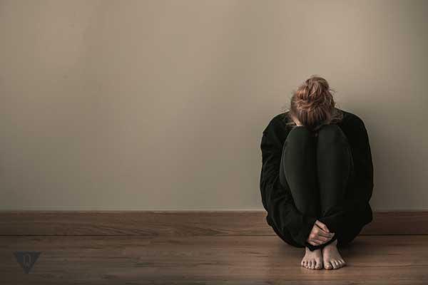 Девушка сидит в комнате расстроенная