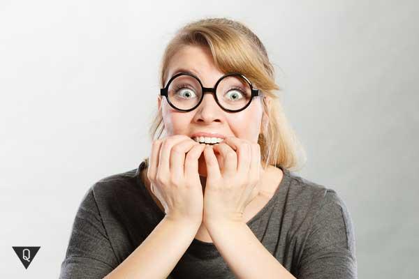 Женщина грызет ногти в страхе