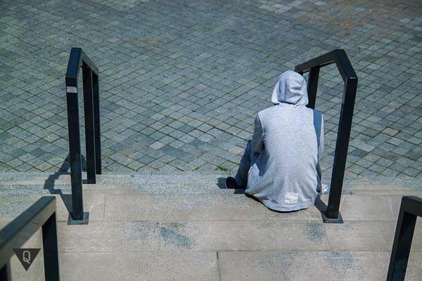 Парень сидит один на лестнице