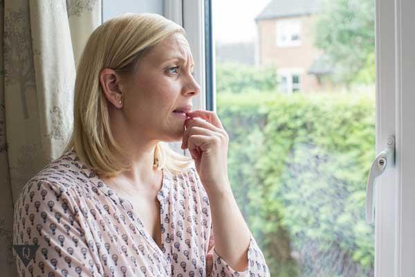 Женщина со страхом смотрит на улицу из квартиры