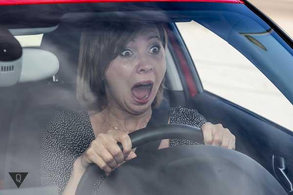 Женщина кричит в ужасе за рулем авто
