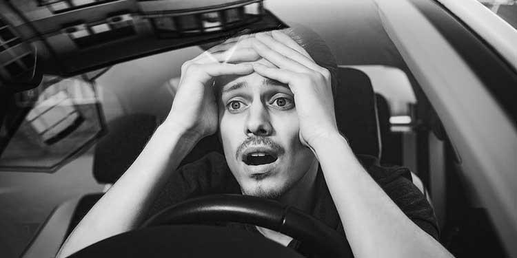 Расстроенный мужчина за рулем автомобиля