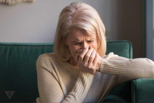 Седовласая женщина рыдает, закрыв рот