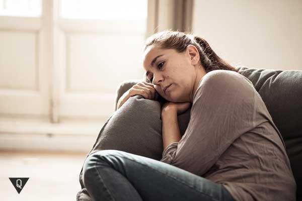 Женщина на диване лежит и о чём-то думает