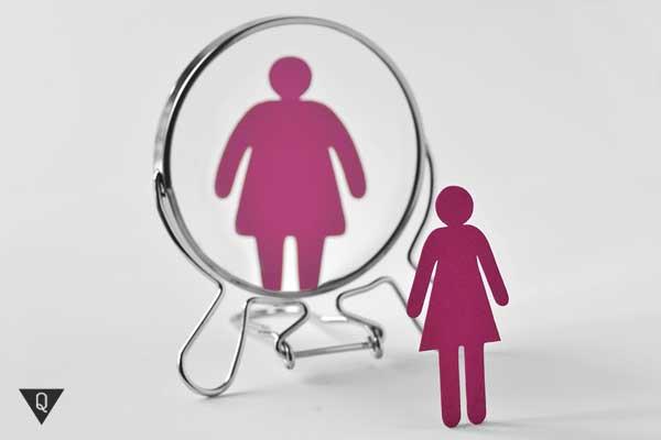 Картонный человечек стоит напротив зеркала