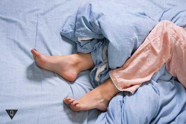 Ноги человека в пижаме на кровати