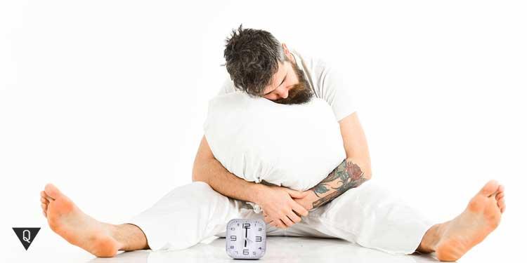 Мужчина пытается сидя уснуть с будильником и подушкой