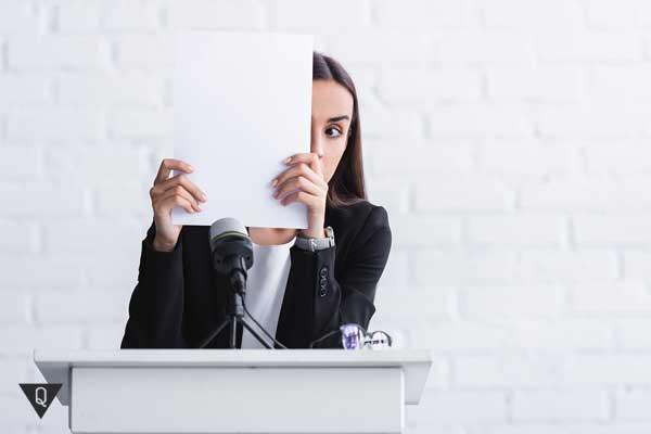 Девушка прячется за листом бумаги