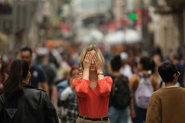 Девушка закрывает глаза в толпе людей