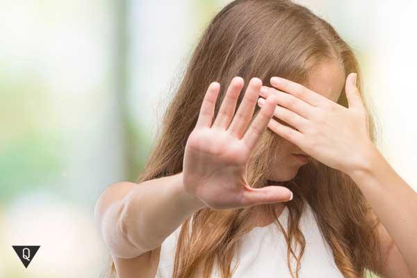 Девушка закрывает глаза и просит жестом не смотреть