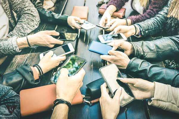 Группа людей сидят в мобильных телефонах