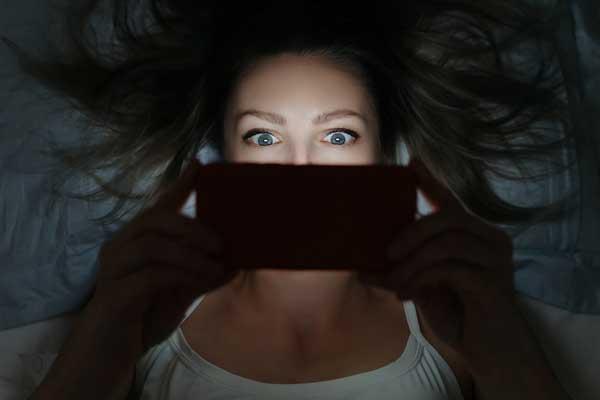 Девушка ночью смотрит в телефон