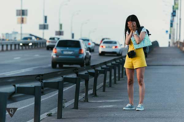 Девушка плачет рядом с дорогой