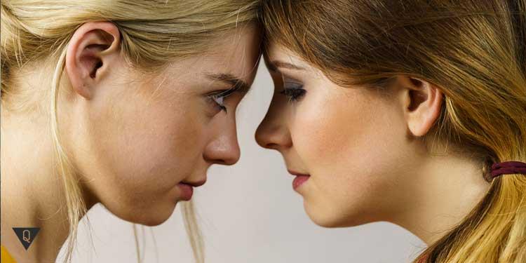 девушка смотрит на другую девушку которая опустила глаза