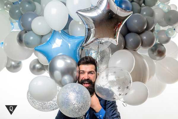 Мужчина с большим количеством воздушных шаров