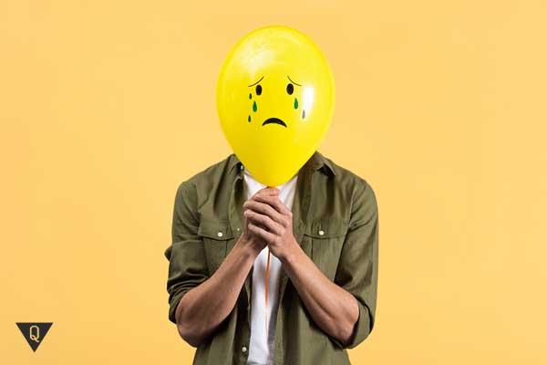Мужчина держит маску из воздушного шарика