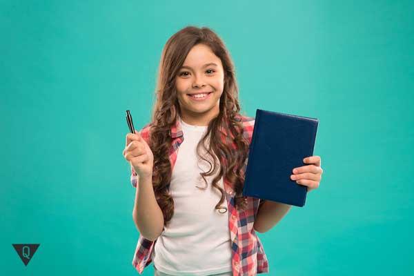 Школьница с тетрадкой и ручкой