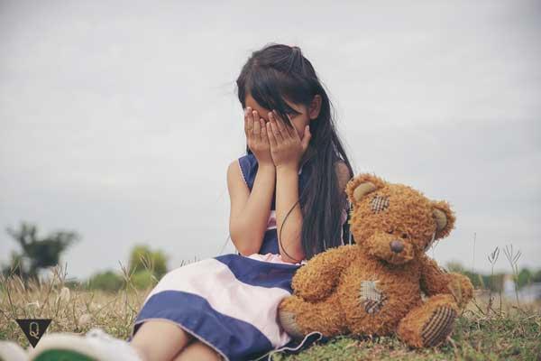 Ребенок плачет рядом с плюшевым мишкой