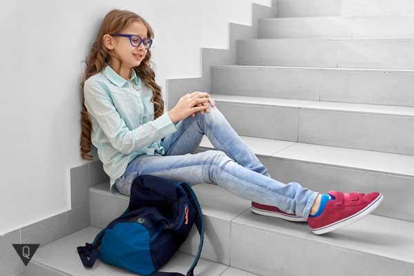 Девочка сидит на лестнице и плачет