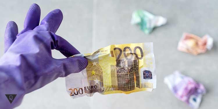 Человек в перчатках держит евро