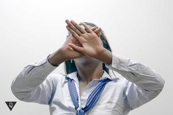 Девушка прячет руками лицо