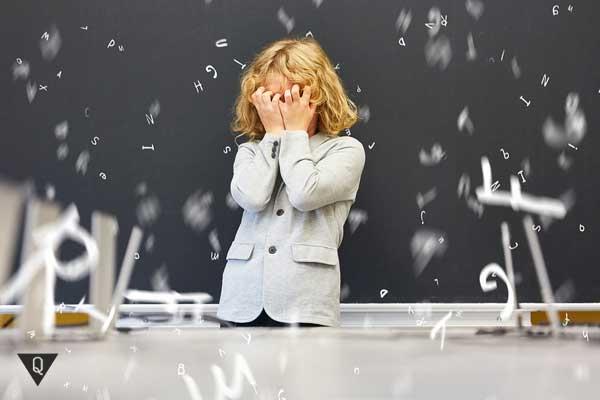 Ребенок возле доски закрыл лицо руками