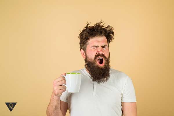 Мужчина зевает с чашкой кофе в руках