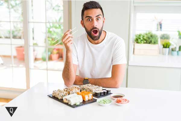 Испуганный мужчина за столом ест суши