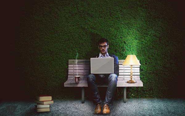 Мужчина работает за компьютером на лавочке