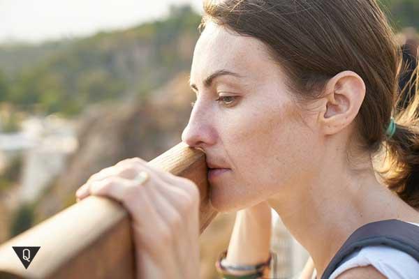 Женщина грустит на мосту