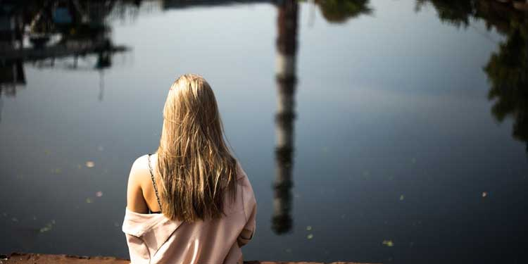 Девушка сидит на мосту